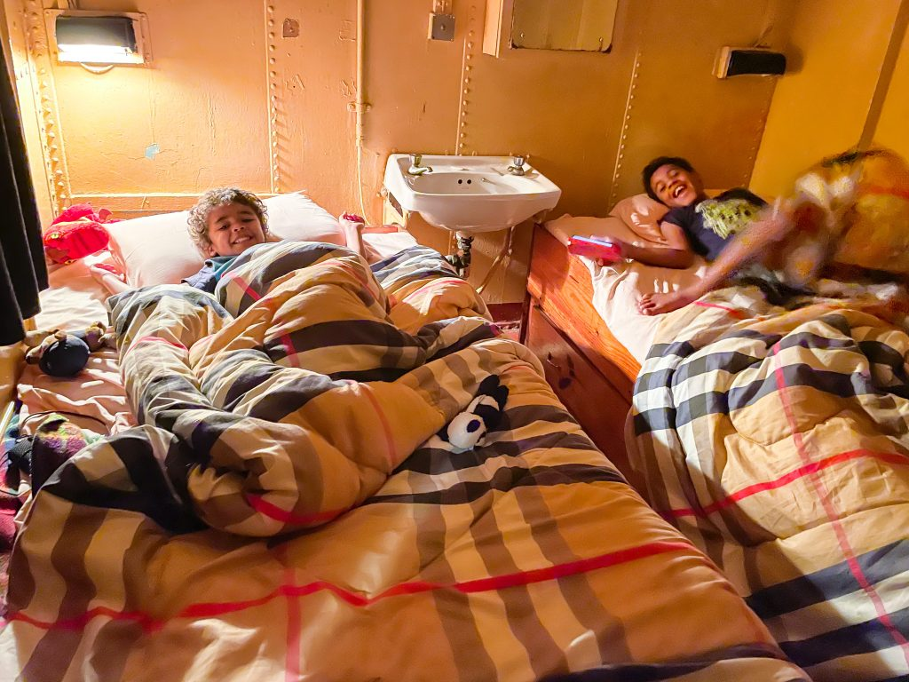 two boys lie in the beds in a standard cabin in the MV Ilala in Lake Malawi