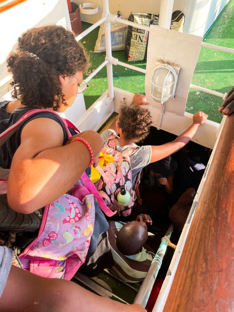 children with backpacks going down stairs on the MV Ilala boat in Lake Malawi to the crowded bottom deck