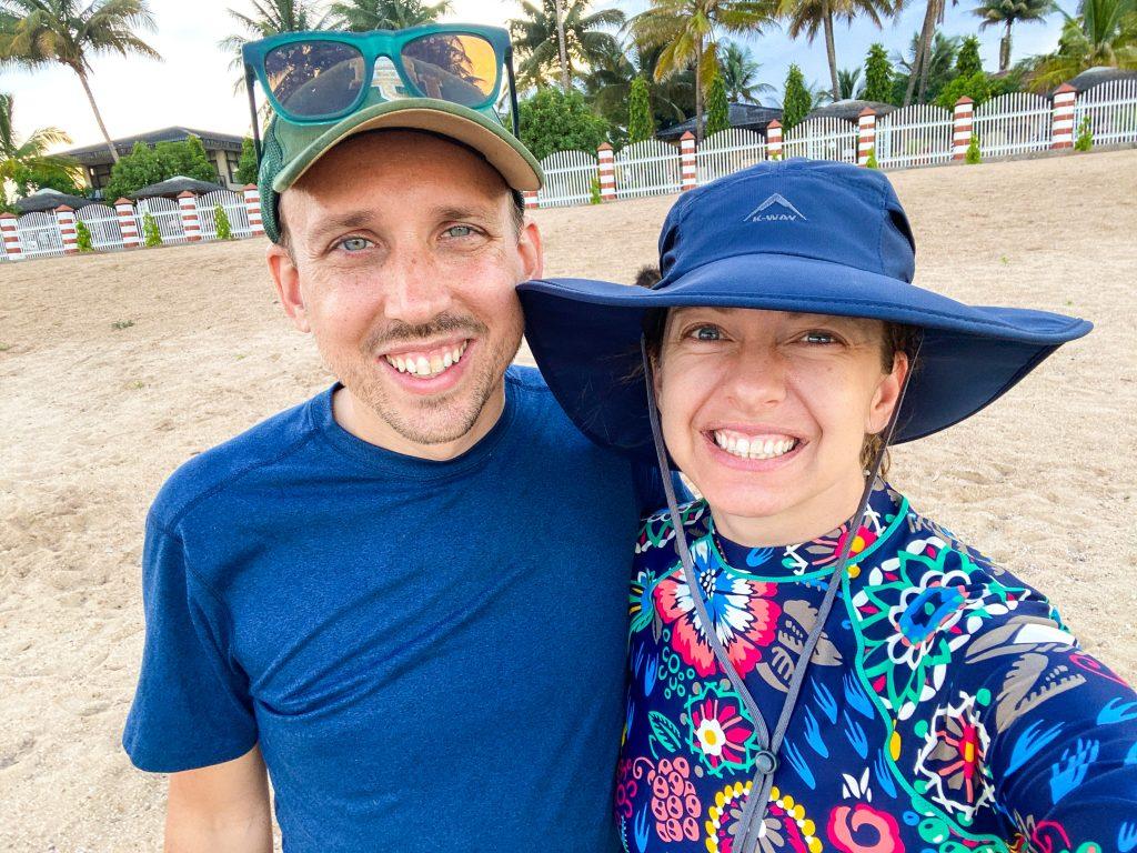 a man and a woman smiling on a beach they are both wearing hats and rash guards Malawi Lake Malawi Mangochi