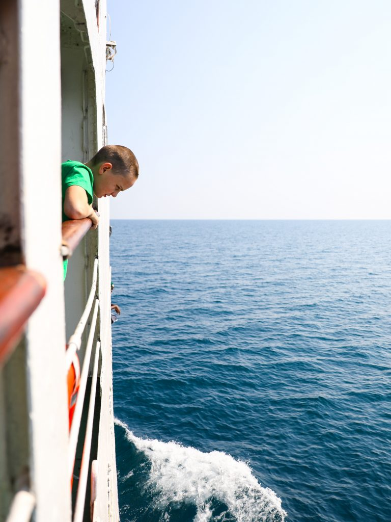 a boy looking over the rail of the Ilala boat in Malawi on Lake Malawi watching the waves as the boat moves