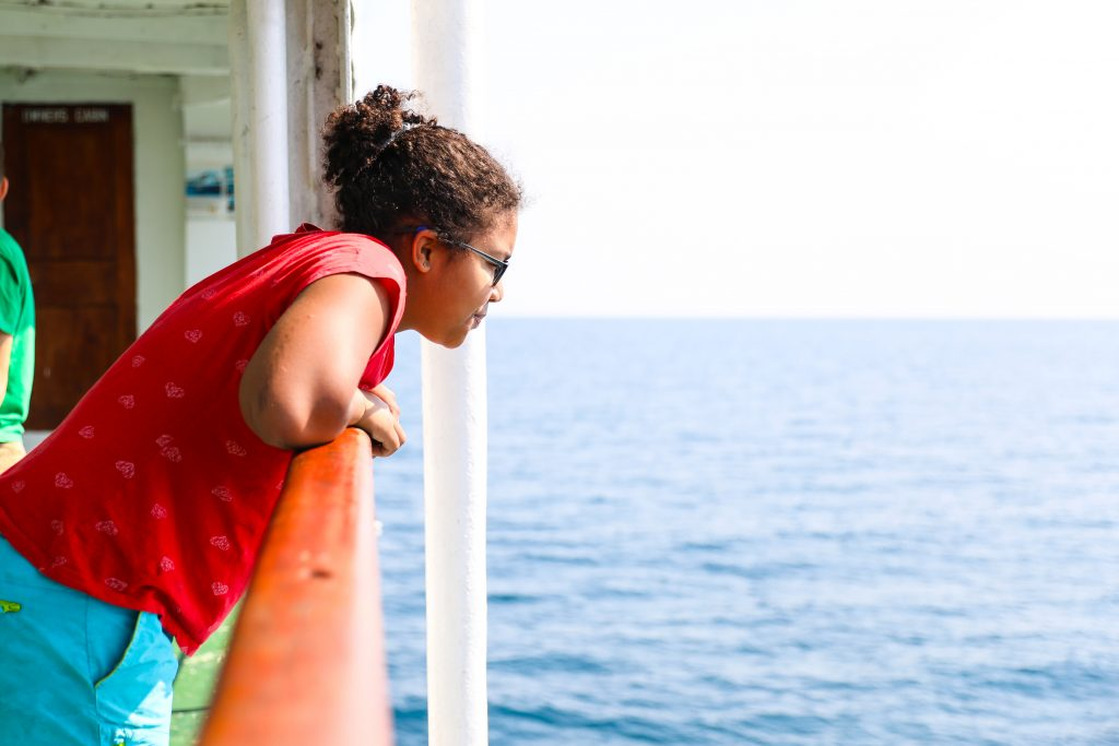 a girl red shirt glasses looks over the rail of the Ilala in Malawi Lake Malawi water