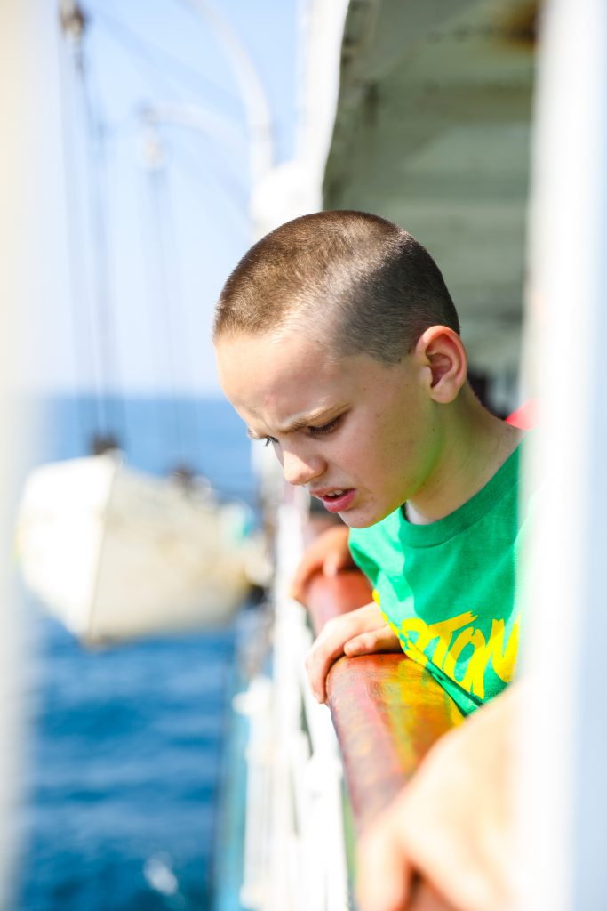 a boy leans over the rail of the MV Ilala boat in Lake Malawi watching passengers get on and off