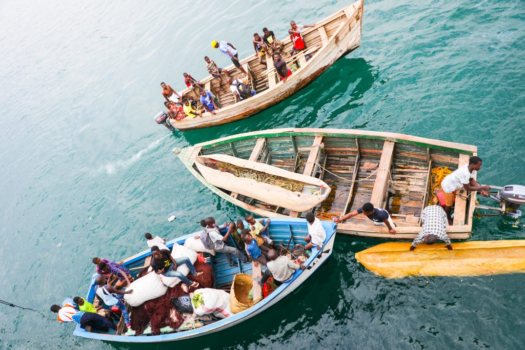 small fishing boats wait by the Ilala boat in Malawi on Lake Malawi full of many people to board and unload people and cargo