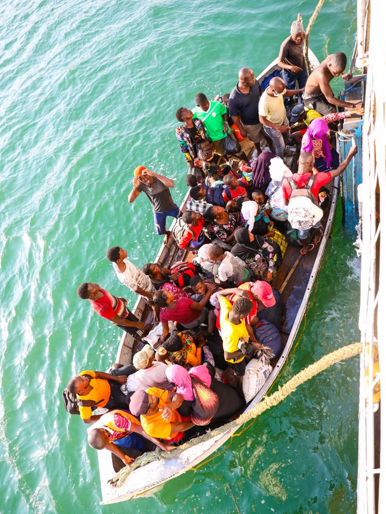 a small fishing boat full of people getting on or off the Ilala boat in Malawi on Lake Malawi