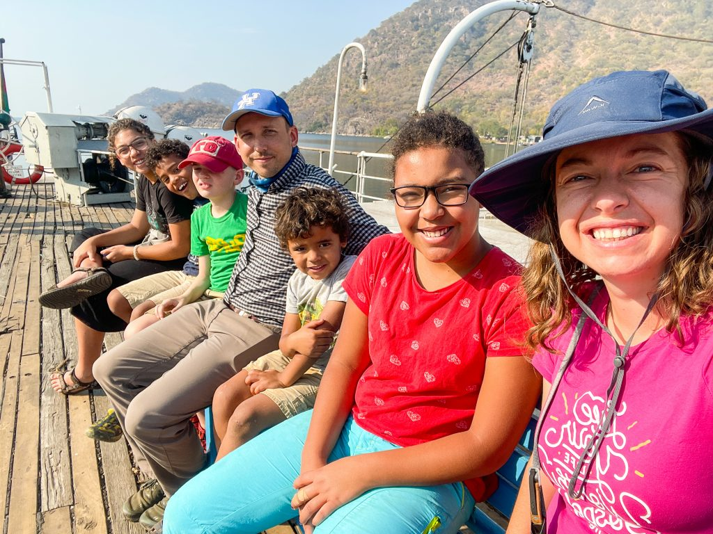a family smiling sitting on a bench on the top deck of the Ilala boat in Malawi on Lake Malawi