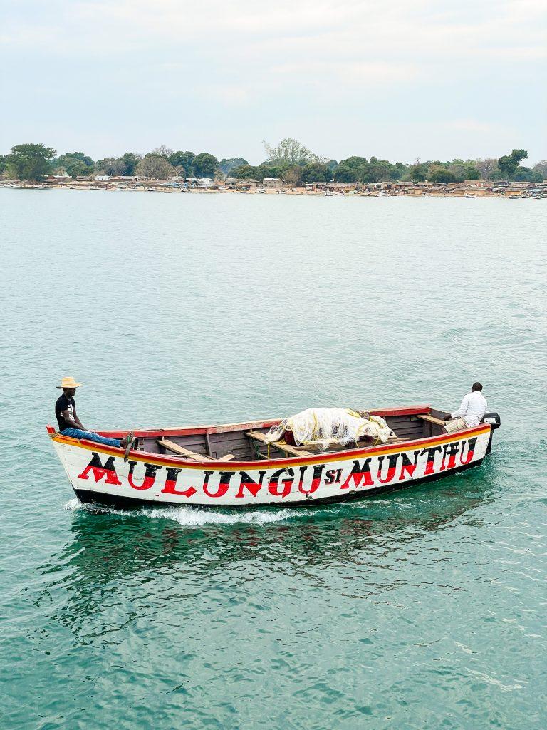 a small fishing boat that says mulungu si munthu god is not a man on Lake Malawi in Malawi at Makanjira waiting to board passengers from the Ilala boat