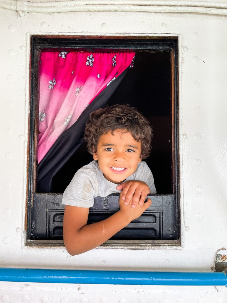a young curly haired boy looks smiles out a small black framed window on the Ilala in Malawi Lake Malawi pink curtain