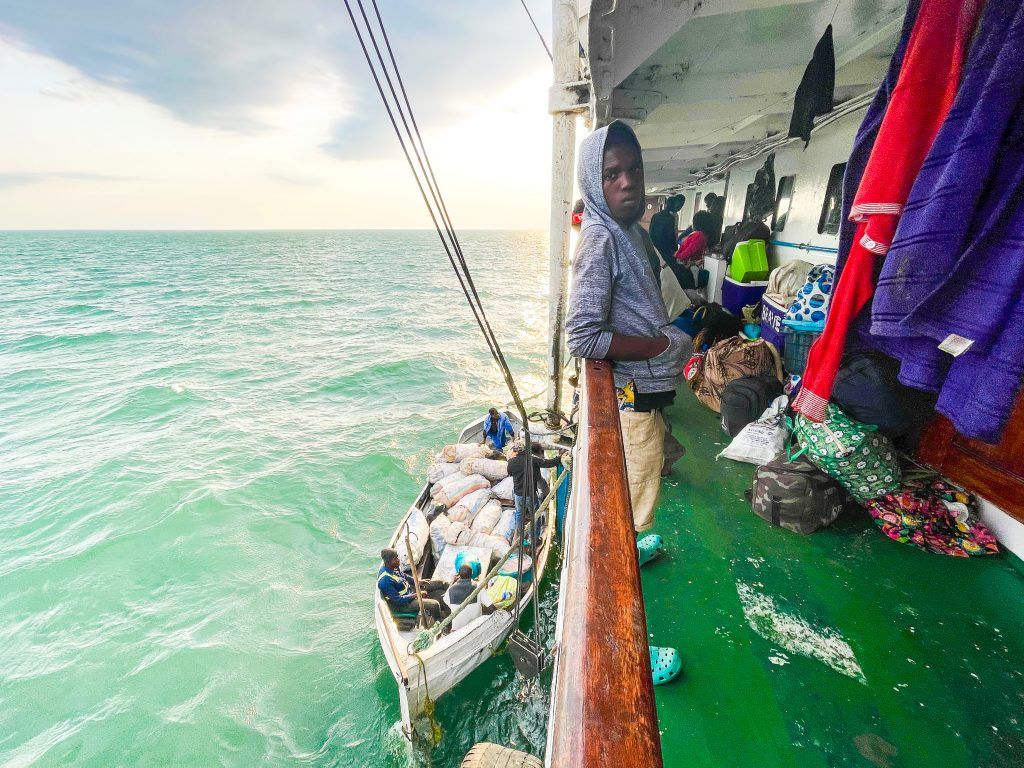 a man stands on the deck of the Ilala boat in Malawi on Lake Malawi the deck is full of people and belongings while below a small fishing boat is being loaded or unloaded with passengers and cargo
