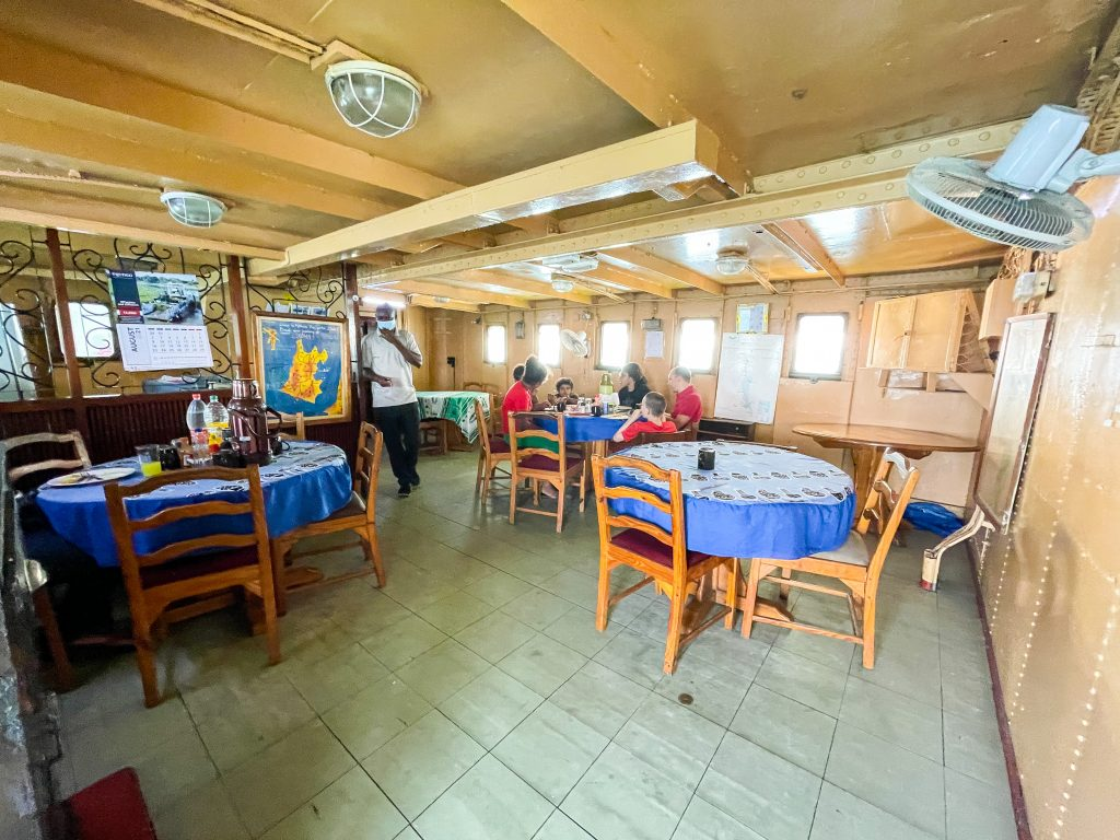 the small restaurant saloon on the Ilala in Malawi on Lake Malawi, some people sitting at round tables