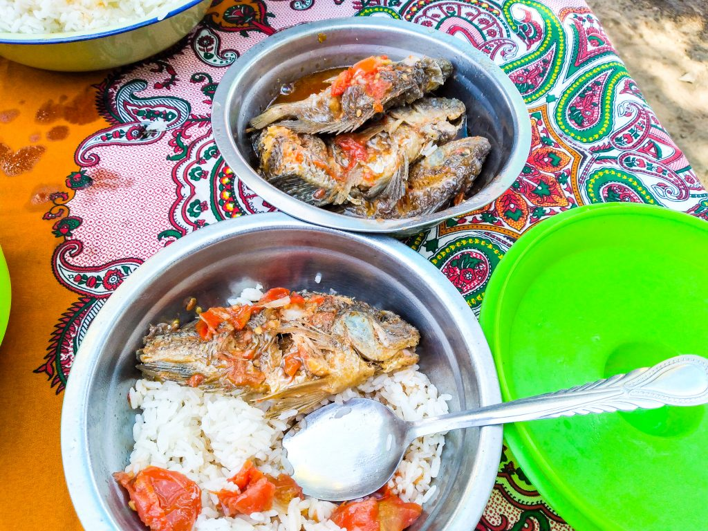 whole grilled fish served in bowls with rice and tomatoes pictured on a colorful chitenge african fabric tablecloth