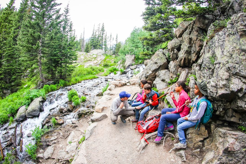 a family stops for a snack break along the trail to emerald lake in rocky mountain national park