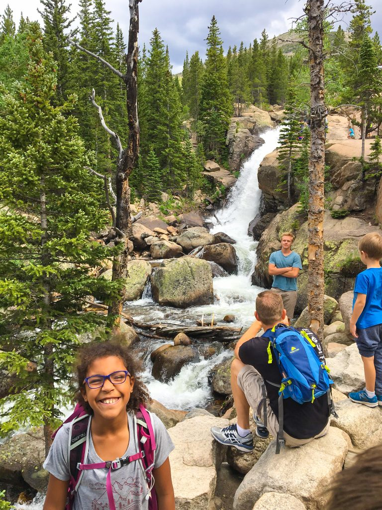 a girl smiles in front of Alberta Falls in rocky mountain national park