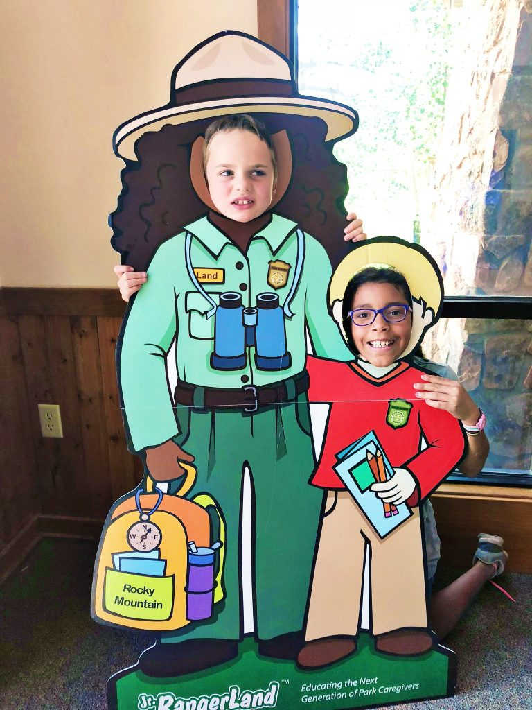a boy and a girl pose at a face cut out stand at Fall River Visitors Center at Rocky Mountain National Park