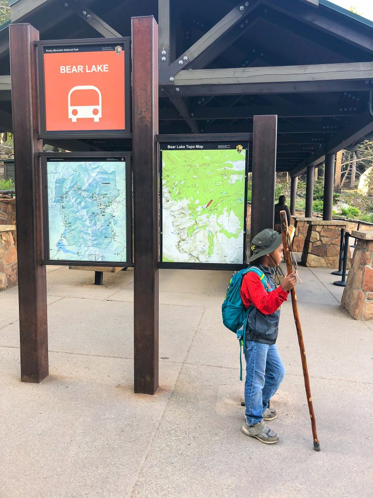 a boy with a hiking stick and backpack stands at the bear lake shuttle lot waiting for a shuttle