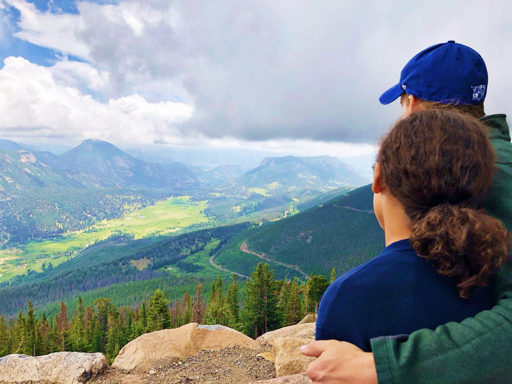 A man and a girl sit at a lookout overlooking sheep lakes at rocky mountain national park