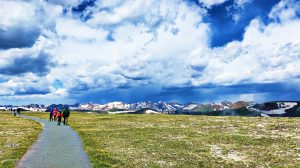 a family hikes a path in Rocky Mountain National Park, snowcapped mountains in the distance, green grass, and blue sky with fluffy clouds