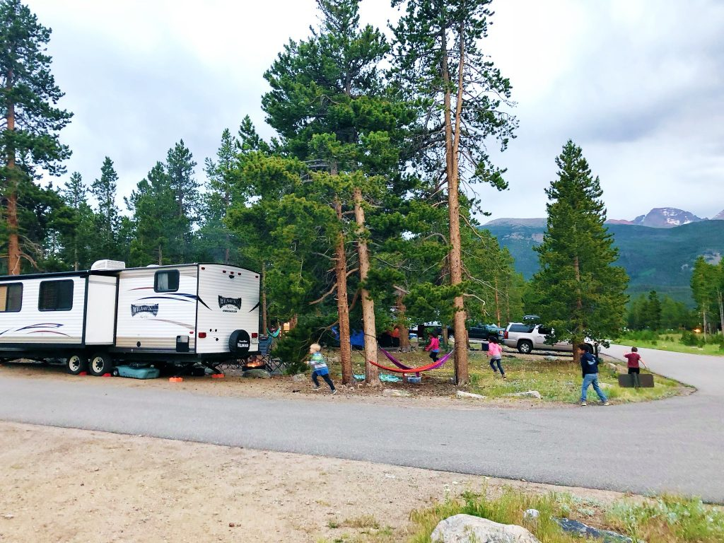 kids play around tall pine trees, hammocks, and a camper at glacier basin campground in rocky mountain national park