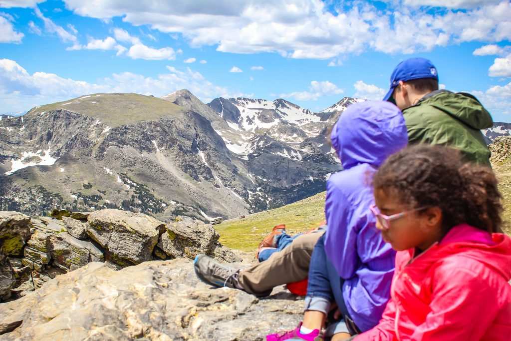 a family sits on rocks overlooking trail ridge road at rocky mountain national park
