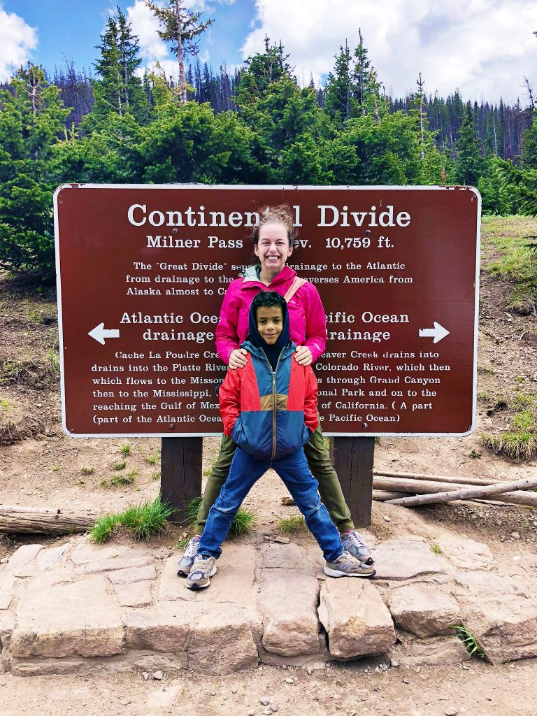 a woman and boy pose in front of the continental divide sign at milner's pass in rocky mountain national park