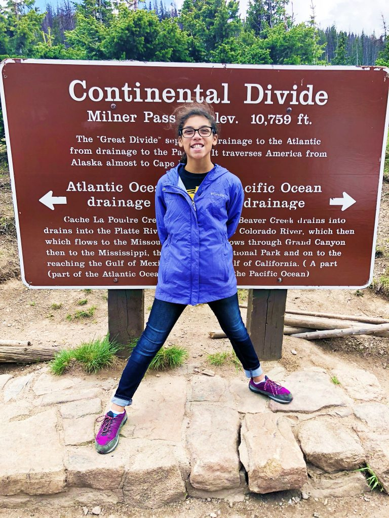 a girl poses in front of the continental divide sign at milner's pass in rocky mountain national park