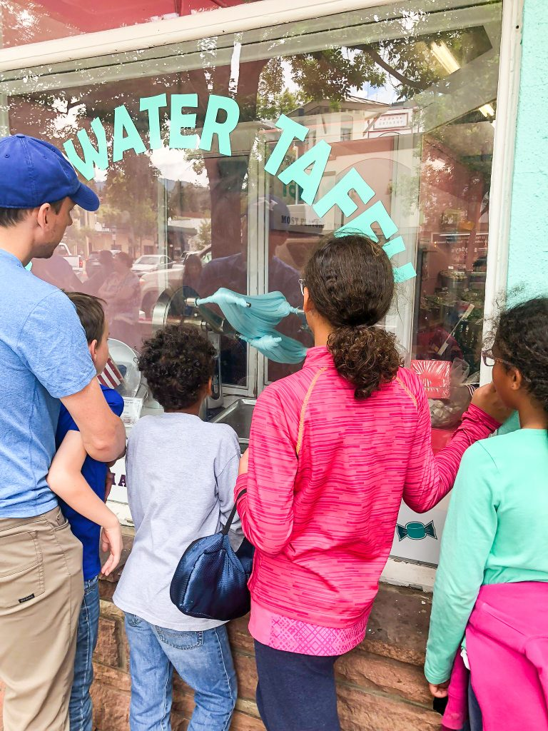 a family watches through the window as salt water taffy is made in estes park colorado