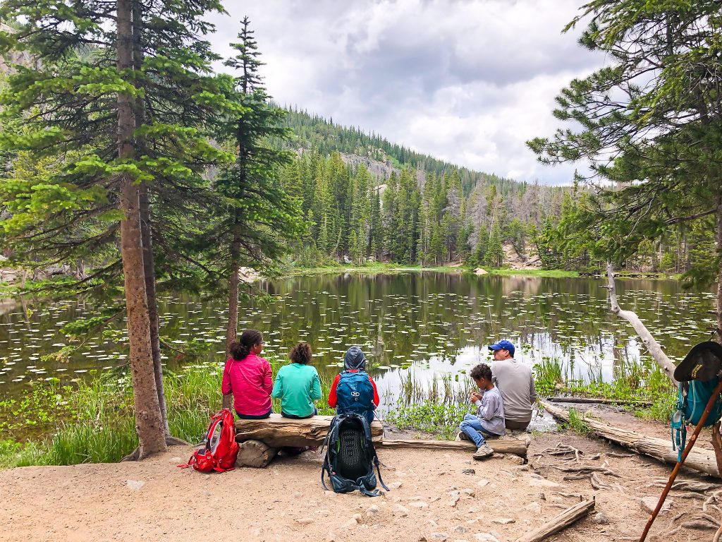 a family stops for a snack at nymph lake in rocky mountain national park