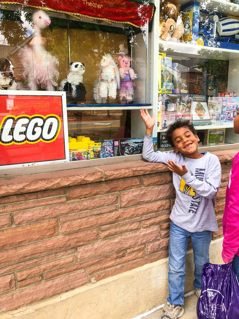 a boy smiles in front of a window display of legos and puppets in estes park colorado