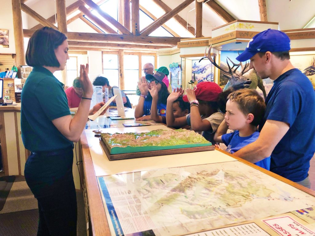 kids getting sworn into the junior ranger program and getting their junior ranger badges at fall river visitors center at rocky mountain national park