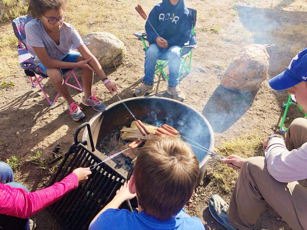 a family sits around a campfire roasting hotdogs at glacier basin campground in rocky mountain national park