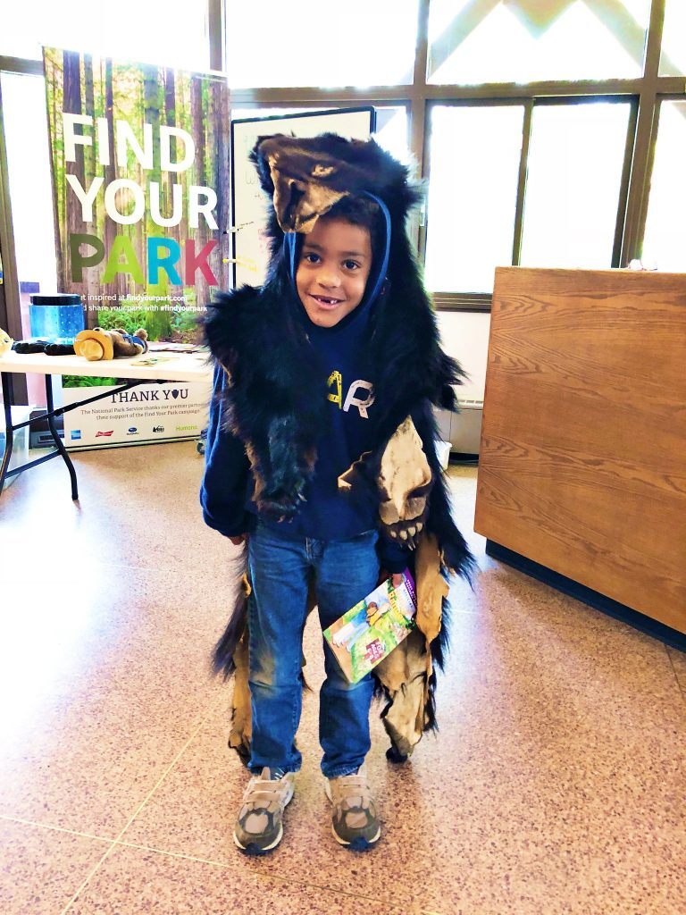 A boy wears a bearskin during a ranger presentation about bears at rocky mountain national park at beaver meadows visitor center