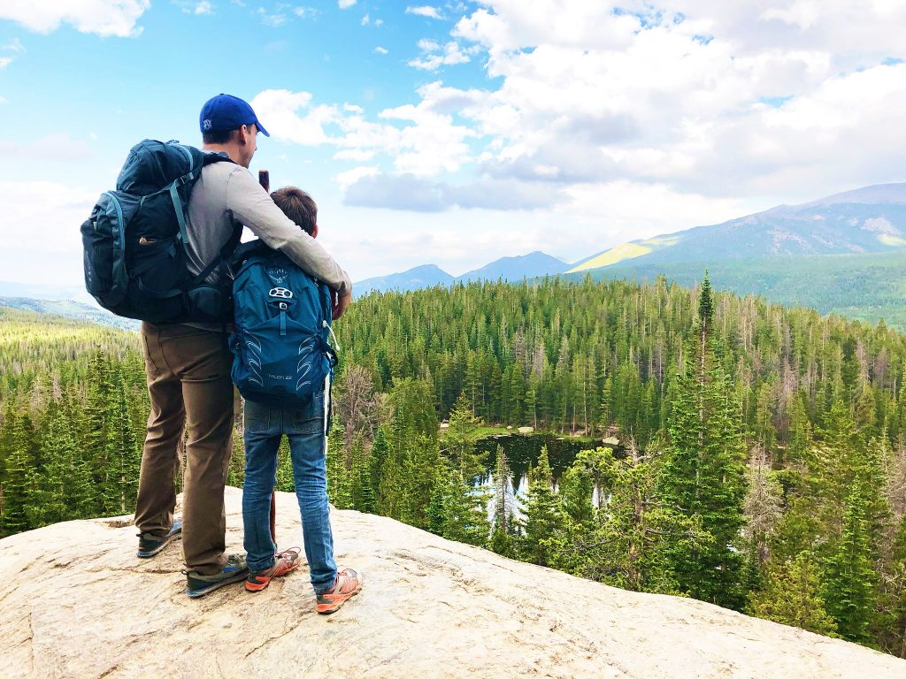 a man and a boy stand on a rock looking over a tree filled valley and a lake at rocky mountain national park