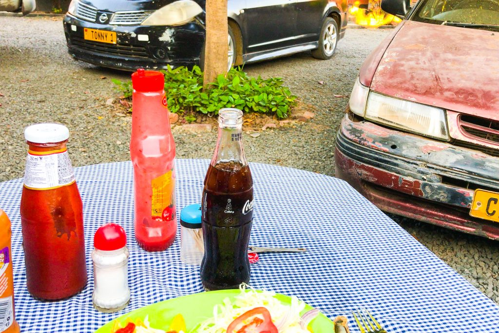 a table with blue and white checked tablecloth, with a few condiments and a coke coca-cola and a plate of food sits outside in the grass beside parked cars