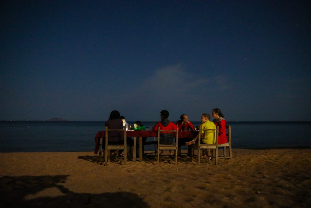 A family eats a candlelit dinner supper at a table on the beach in the dark at Mango Drift Lodge on Likoma Island in Lake Malawi