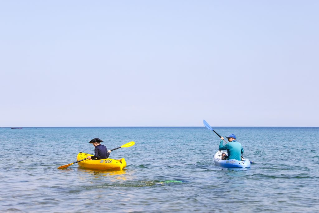 A boy in a yellow kayak and a man in a blue kayak paddle away from shore at Mango Drift Backpacker's Lodge on Likoma Island in Lake Malawi