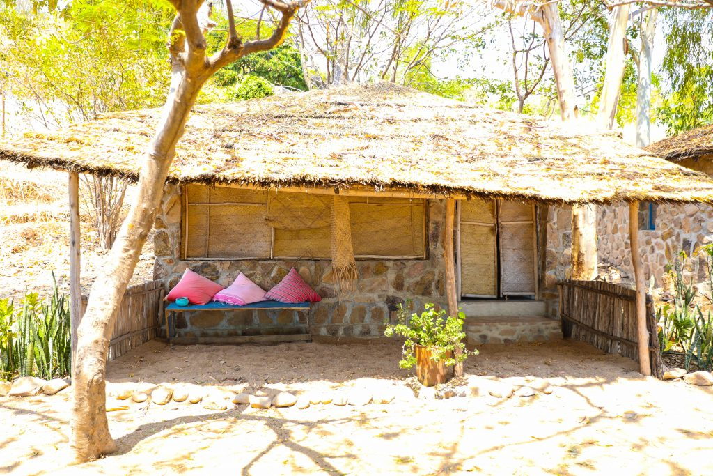a beachfront beach chalet room with a grass reed roof and covered porch sits on the beach at Mango Drift on Likoma Island in Lake Malawi