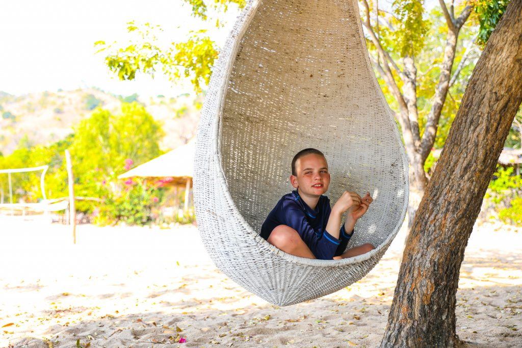 a boy swings in a large white cane rattan egg chair hanging from a tree on the beach at Mango Drift Lodge on Likoma Island in Lake Malawi