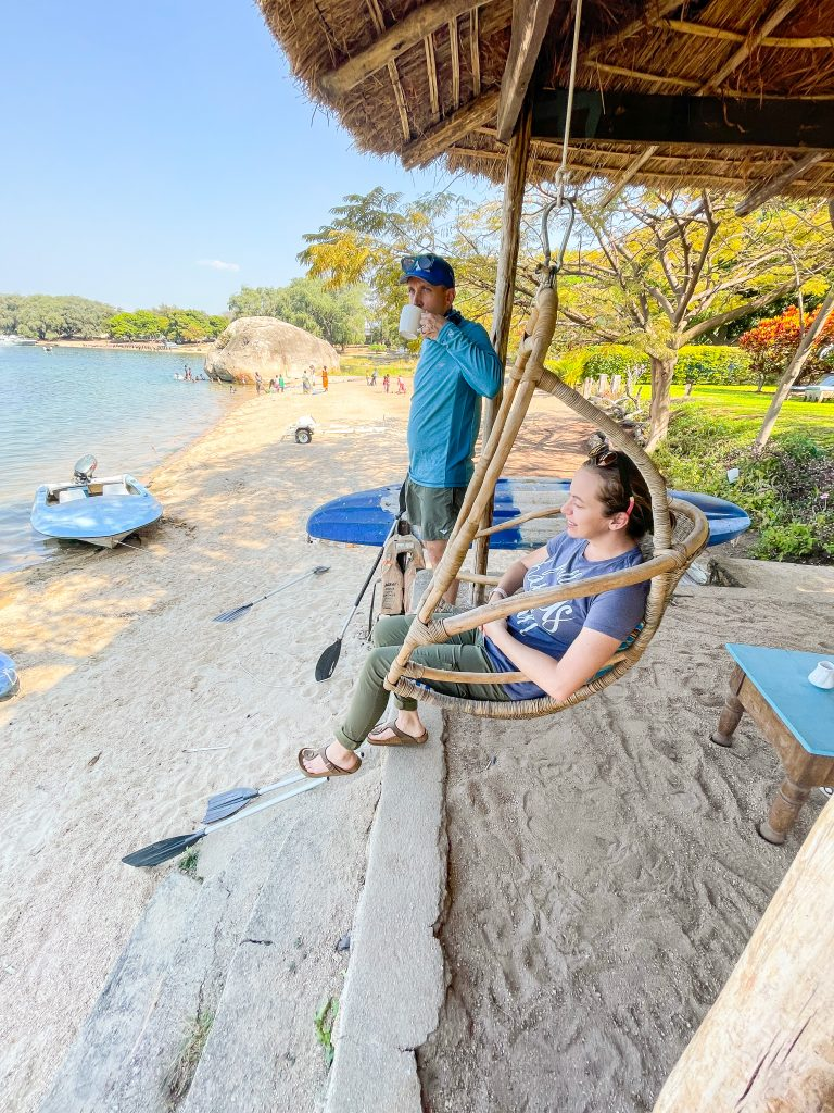 A man stands drinking coffee and a woman sits in a hanging egg chair at Monkey Bay Beach Lodge in Malawi on Lake Malawi enjoying the beach view