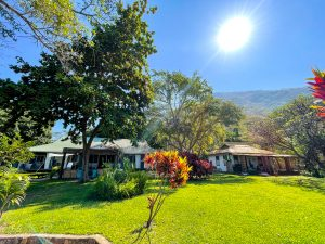 Monkey Bay Beach Lodge in Malawi on Lake Malawi sits in front of a hill with a bright sunny sky and large grassy lawn