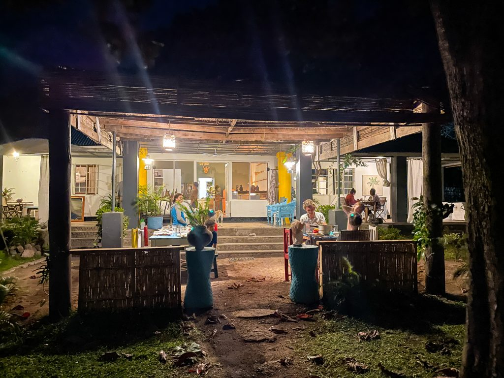 The outdoor dining area of Monkey Bay Beach Lodge on Lake Malawi, a few families are eating dinner outside at night