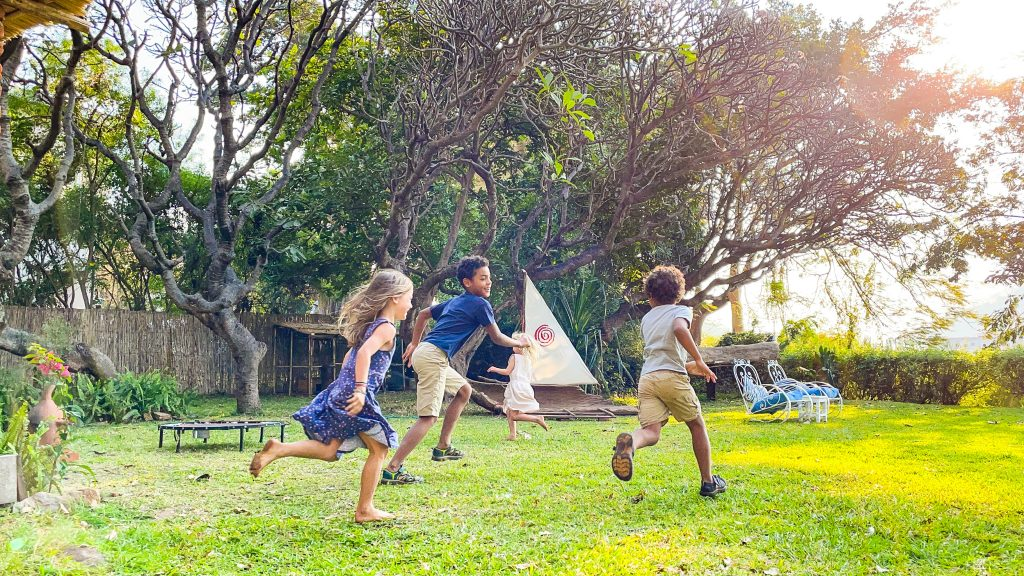 two boys and two girls play on the grassy lawn at Monkey Bay Beach Lodge on Lake Malawi
