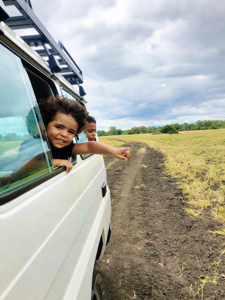 on safari at Liwonde National Park in Malawi a boy sticks his head out the window of a white land cruiser and points to an animal