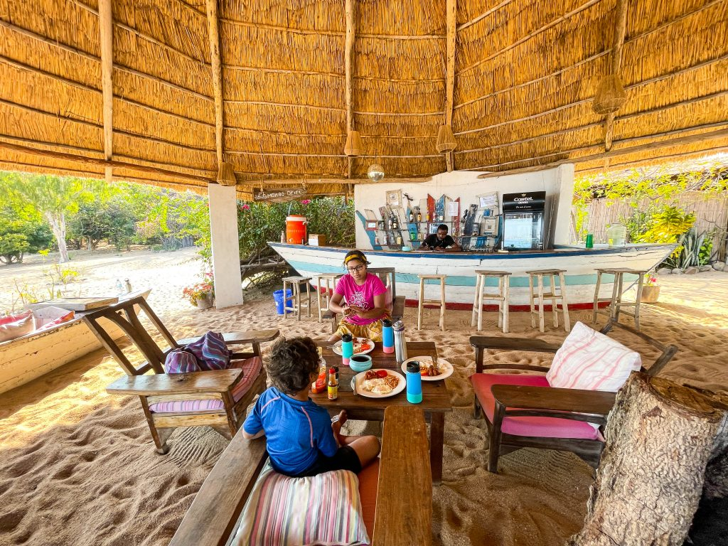 two kids sit in the lounge area as breakfast is served on the beach under a grass reed roof at Mango Drift Lodge on Likoma Island in Lake Malawi. An old boat turned into a bar is in the background.