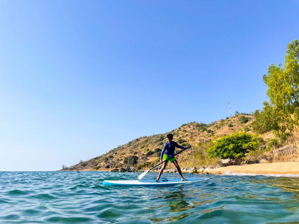 A boy stands on a stand up paddleboard sup on Lake Malawi near the beach at Mango Drift Lodge on Likoma Island