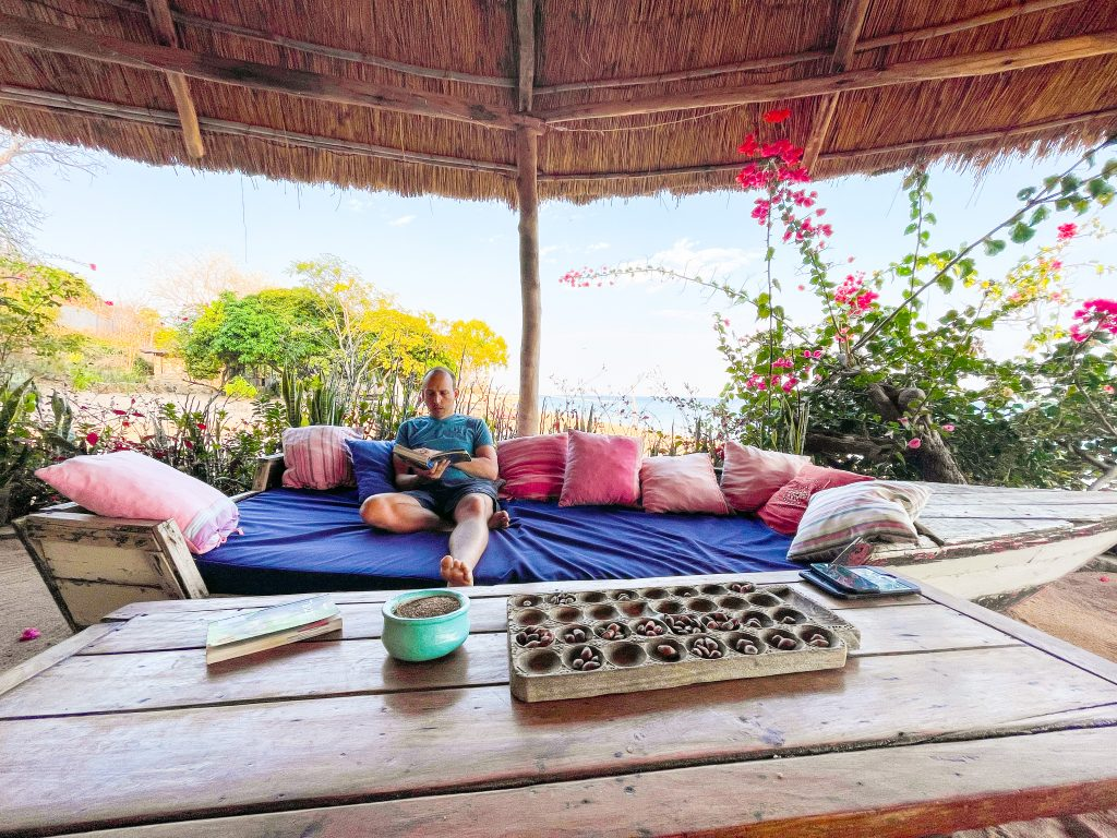 A man sits in the grass roof covered lounge area of Mango Drift Lodge on Likoma Island in Lake Malawi in an old boat turned into a couch, with a coffee table in front that holds a bawo bao board game