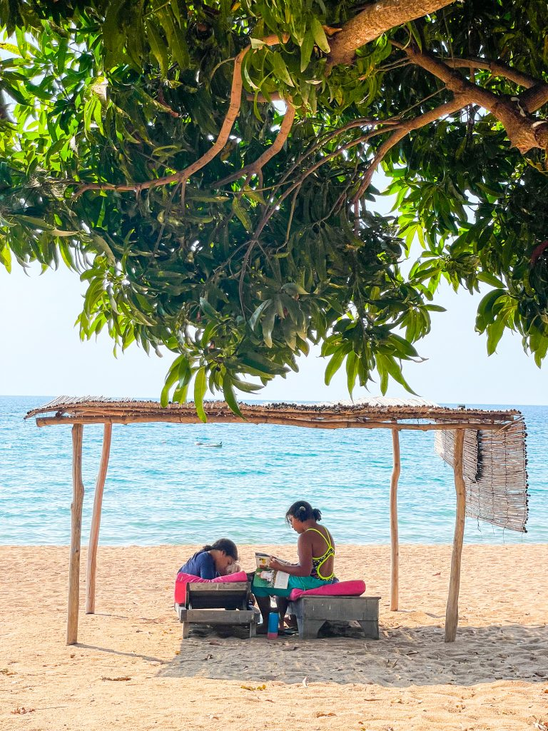 two girls sit on lounge chairs with pink cushions on the beach under a reed grass covered area reading magazines at Mango Drift on Likoma Island in Lake Malawi