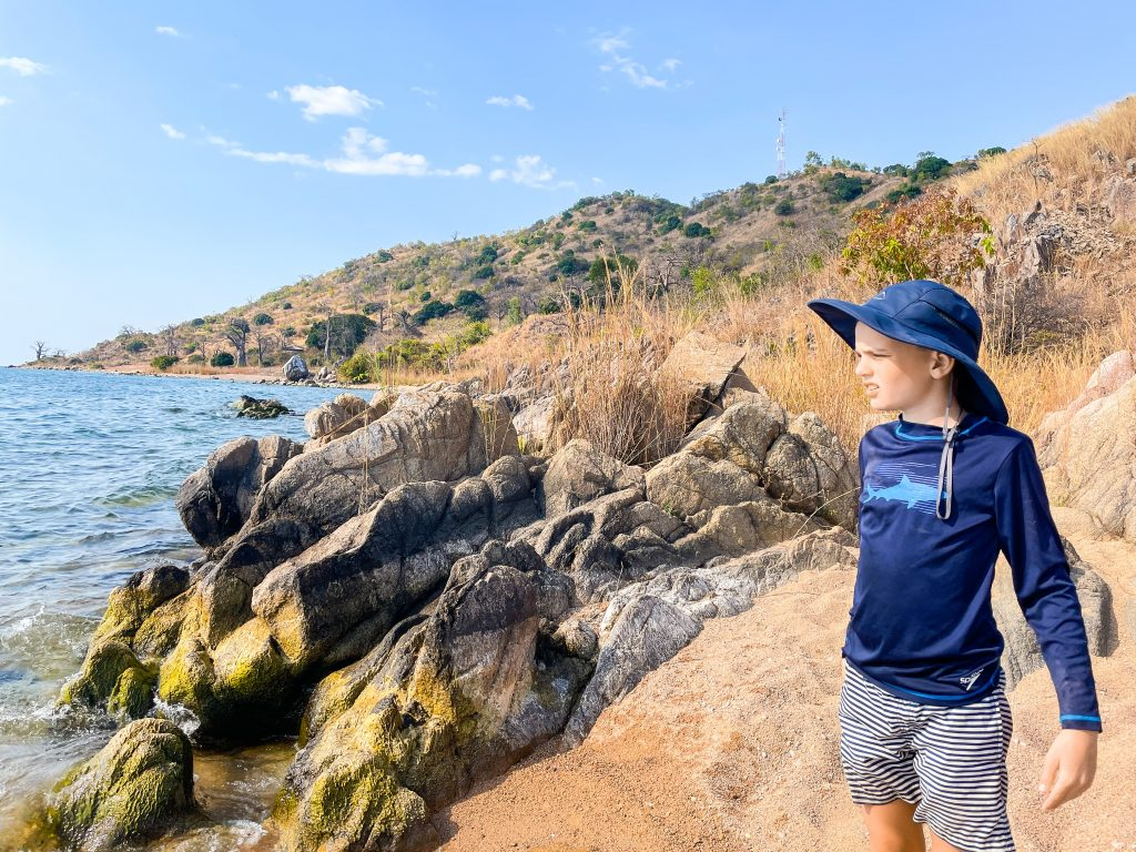 A boy in striped swim trunks shorts and a navy rash guard and sun hat stands on the beach by some rocks with rocky hills in the background looking over the water at Mango Drift Backpacker's Lodge at Likoma Island in Lake Malawi