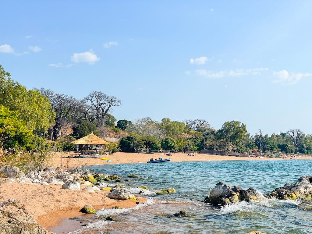 A view of Mango Drift on Likoma Island in Lake Malawi from the rocky beach beside the lodge. A grass roof hut and a boat sit on the beach