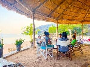 kids sit around a table at Mango Drift Lodge on Likoma Island in Lake Malawi in an outdoor eating area on the beach