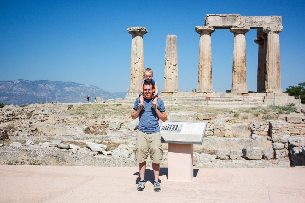 A man stands with a boy on his shoulders in front of the temple of apollo in corinth, greece