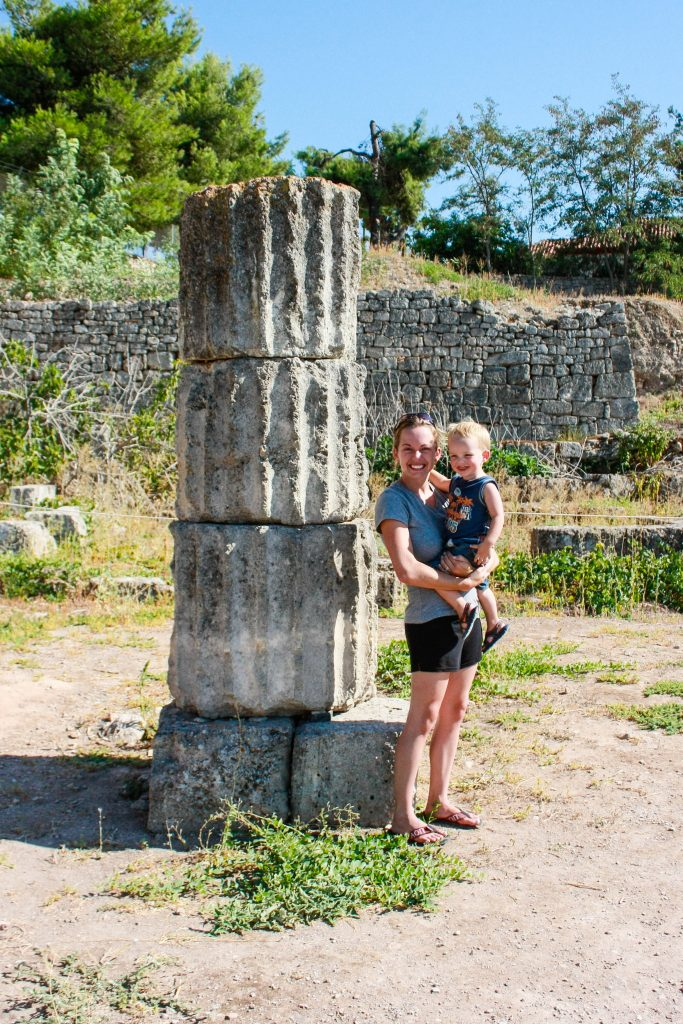 a woman and a boy stand beside a column ruin in ancient corinth, greece